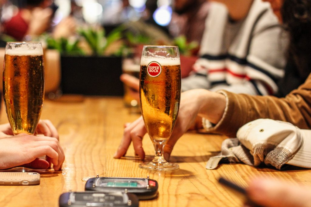 people serving beer with phone on the table while serving beer by izhak agency